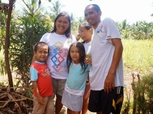 サトウキビ畑のためのローンを申請している女性とその家族。両親にはさまれた白いシャツの女の子が高校を首席で卒業した娘