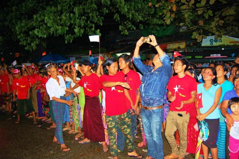 党旗を振りかざすNLDの支持者たち。集会で道路は大渋滞で周辺も混雑していた