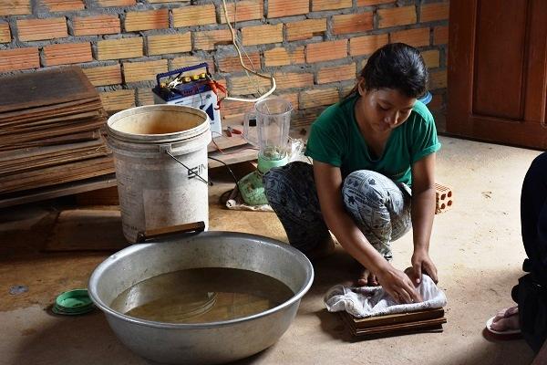 バナナの繊維を水に溶かし、紙すきをする10代の女性スタッフ