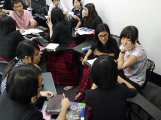スタラティジー・ファーストに通う女子生徒たち。黒のエンヂーと赤いロンジーの制服を着て授業を受ける