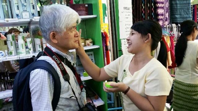 ヤンゴンのマーケットでミャンマーの子どもや女性が使う日焼け止め兼化粧品の「タナカ」を試しに塗ってもらう様子。懐の深いミャンマー人は微笑むとみんなはにかんだ素敵な笑顔を浮かべてくれる。昔の日本人を感じさせるような控えめな人が多い