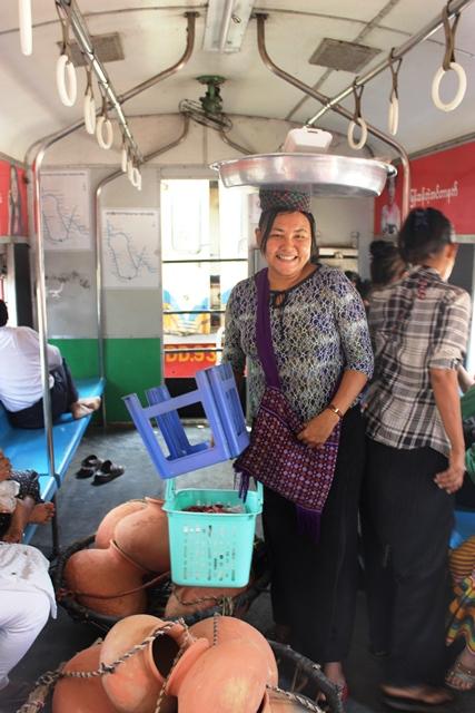 頭に乗せたお菓子を売るエッエッさん。ミャンマーのヤンゴン環状鉄道の中で