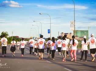 0719中田さん、まだ西日の強い夕方のメコン河沿いを参加者たちが歩いていく