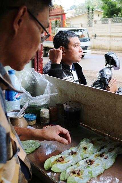 タウンジーの道端で噛みたばこ(クーン)を売るウサンニさん。20年培ってきた手さばきは鮮やか。10個のクーンを30秒で作る
