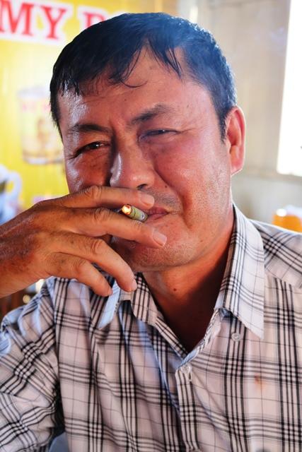 嬉しそうに葉巻(セーボレイ)を吹かす愛煙家のタイヤンさん。「自分以外の家族全員がたばこを嫌っているので、家では肩身が狭い。外でしかセーボレイを吸えない」(ミャンマー・タウンジーで)