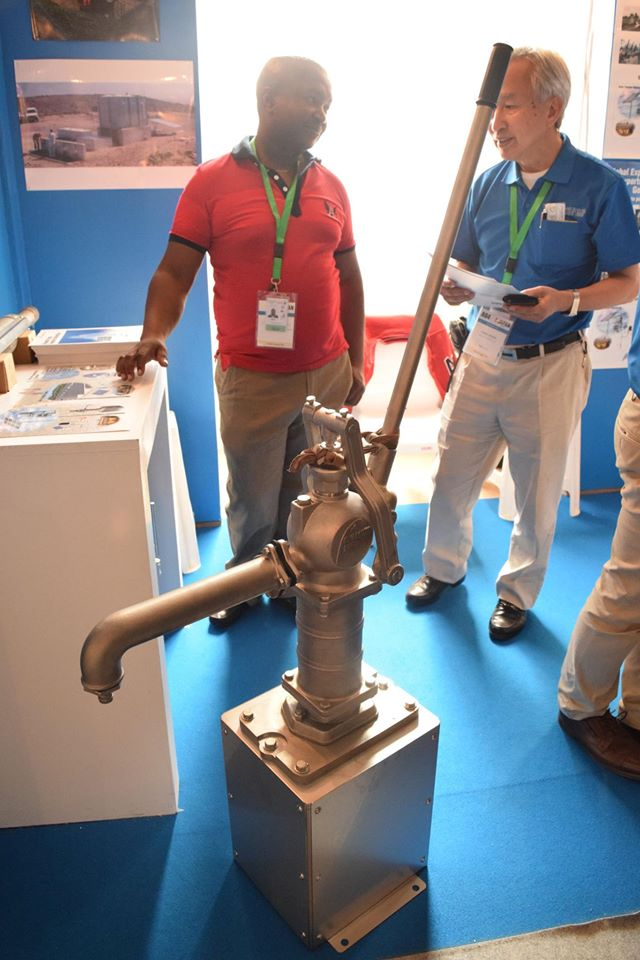 TICAD VIの公式サイドイベント「ジャパンフェア」でタンデム式ソーラー手押しポンプの利点を説明するおかもとパイプの社員。アフリカの人たちが興味深くポンプを見つめていた