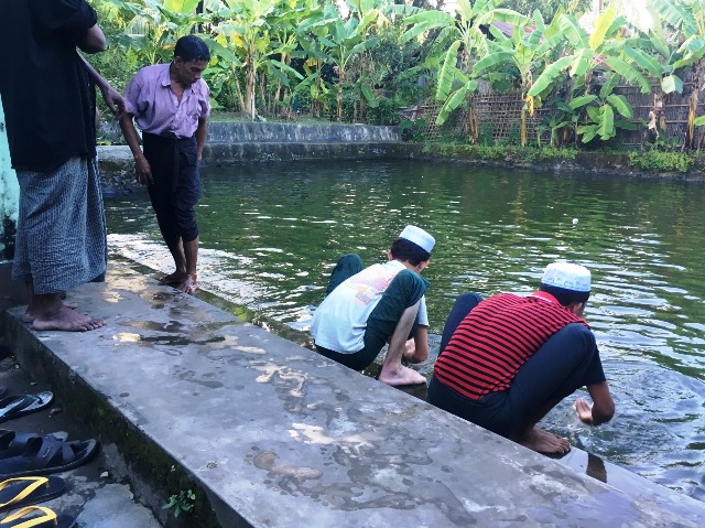 居住区で一番立派なモスクの中には、身を清めるための池がある。礼拝の前に手足を洗うロヒンギャの男性たち