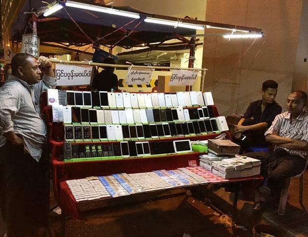 ヤンゴン市内の路上で各種の中古スマホを販売する露店。値段も3万チャット(約3000円)ほどからとお手頃。ミャンマーでは数年前までSIMカードが1枚数万円もしたため、携帯電話は庶民の高値の花だった