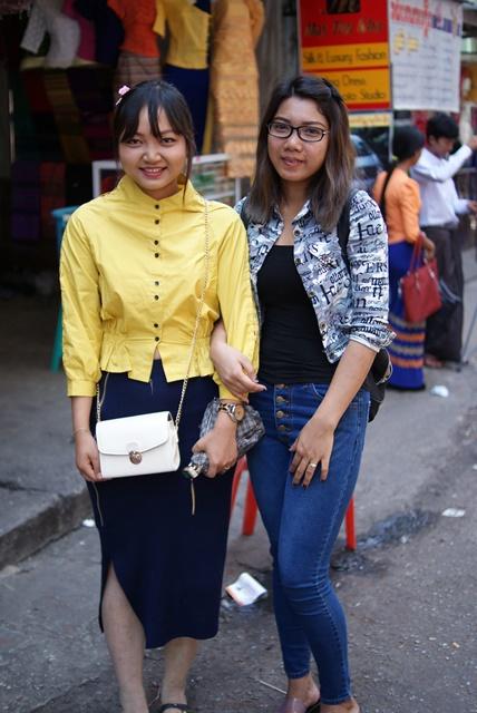 ウートゥンリンチャン通りを歩いていたスカート姿・パンツ姿の女性。背後に見える女性は会社の制服のロンジーを着ている(中里駿之介撮影)