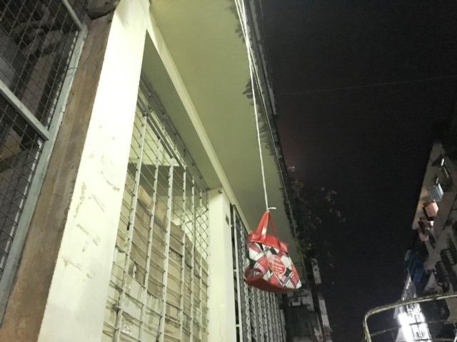 上の階から垂れ下がるヒモの先にはクリップがついており、袋がつりさげられているものもある(ヤンゴンのダウンタウン)