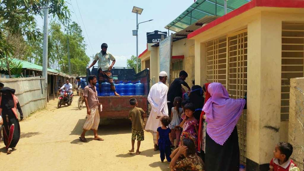 炎天下の中、NGOからが配給する飲料水を待つロヒンギャの人たち。女性と子どもが多いのが印象的だった(レダ難民キャンプ)