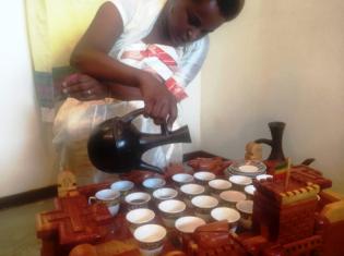 2杯目のコーヒーを注ぐブリファニさん。コーヒーテーブルは、エチオピアの世界遺産ファジル・ゲビ(エチオピアの都市ゴンダールにある王宮群が立ち並ぶ小高い丘)を模したもの。テーブルの左端には乳香、真ん中にはコーヒー豆が置かれている