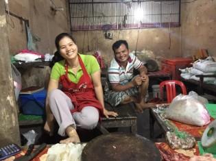プサールー市場で夫婦で豚肉屋を営むナオイさん(左)と夫マオさん(右)。「長年一緒にいるから喧嘩もしなくなったの」と仲良く笑いあう