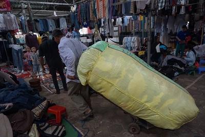 古着を業者が重そうに倉庫へ運ぶ(カンボジア・シェムリアップのルー市場で)