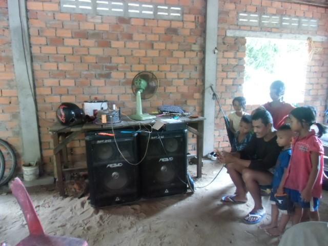 近所の子どもたちが大きなスピーカーのある家に集まり、音楽を聴いたりスマホを見たりする