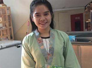 ラッキーモールの総菜屋で働くクロワットさん(21歳、女性)。来世では美しく、良い香りのする女性になりたいという願いを込めて、いつも仏様には蓮の花を手向けているという