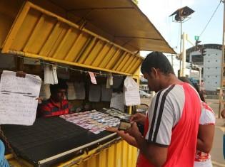 スリランカでは買いたい宝くじの番号を自分で選べる。店の前は、当たりそうな番号の宝くじを探す客で賑わう