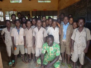 ヘカメ小学校で教師を務めるベフェ・セージさん(前列中央)と子どもたち。ヘカメ小学校の校舎は日本の援助で建てられた。教室は8つある(ベナン・アトランティック県)