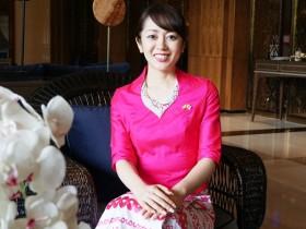 民族衣装をまとったすわじゅんこさん。胸元には日本とミャンマーの国旗が光る(ミャンマー・ヤンゴンで撮影)