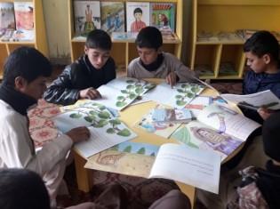 アフガニスタン東部でシャンティ国際ボランティア会が運営する「子どもに優しい空間」で絵本を読む子どもたち(写真提供:シャンティ国際ボランティア会)