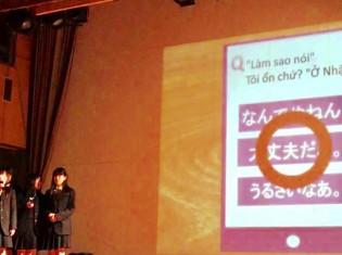 「PalAsia」を発表する滋賀県立守山高校生の4人。PalAsiaでマンガを読むと、スクリーンのように問題が出てきて、答えをクリックすると正解が表示される。写真は、「日本語で『大丈夫です』はなんと言うでしょう?」というベトナム語でのクイズを紹介しているところ(「40億人のためのビジネスアイデアコンテスト」で撮影)