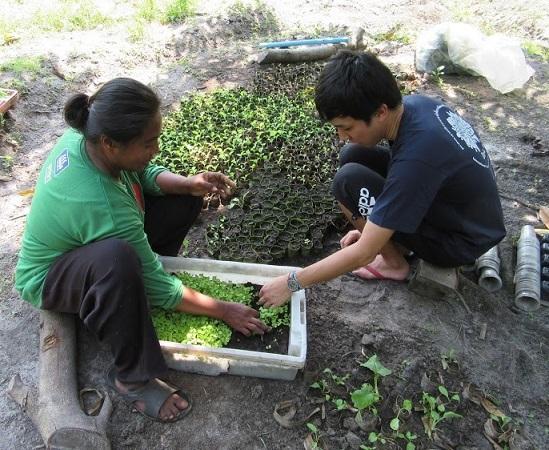 農作業をするジャタックさん(左)。働いたあとはいつも「ヒウカーウ!(お腹すいた~!)」(タイ・スコーン島で撮影)