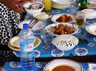 西アフリカの国ベナンのレストランの食卓。左奥にある白い餅のような食べ物がフフ(ベナンでは「アグ」と呼ぶ)。中央に並ぶ魚や肉、スープと一緒に食べる(ベナン・コトヌーで撮影)