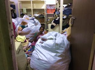 SWaCHに届いたばかりの古着を選別するアウティさん。彼女の仕事場は古着のにおいが立ち込める(インドのプネーで撮影)