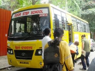 車輪の学校が使うバスは、地元企業などが寄贈した改装車。座席は取り外され、布を敷いた床の上で子どもたちは学ぶ。窓には教材ポスターが貼られ、運転席の背面は黒板、網棚は戸棚にリフォームされている(インド・プネーで撮影)