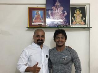 ヒンドゥー教の神のひとつガネーシャの前でポーズをとるレスリング選手のビクラムさん(右)と、有望な選手の発掘・サポートを担当するダナンジャイさん(左)。インド・プネーにある、貧しいアスリートをマネジメントするNGO「ラクシャ」の事務所で撮影