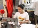 カンボジア・シェムリアップのプサ・ルー(ルー市場)の一角で仕立屋を営むティダさん。一家を支えるために始めた。現在は3人きょうだいで経営する