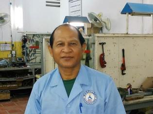 カンボジア・シェムリアップのリハビリセンターで義足を作るキム・エアンさん。後ろは工房
