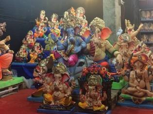 ガネーシャ祭りでは、一家にひとつガネーシャ像を買うのが習慣だ。中央が青い肌のガネーシャ。右下はスワミという僧の座り方をするガネーシャ