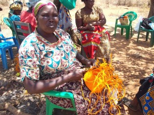 サイザル製のインテリアバスケットを編むケニア人女性。サイザルは「貧乏人の味方」と形容されるほど、乾燥に強く、どこでも育ち、また繊維がとれるため用途が多い有用な植物(写真提供:アンバーアワー)