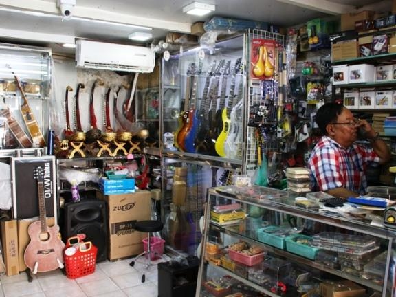 ギターが並ぶ楽器屋の奥に演奏用の竪琴が並ぶ(ミャンマー・ヤンゴン)