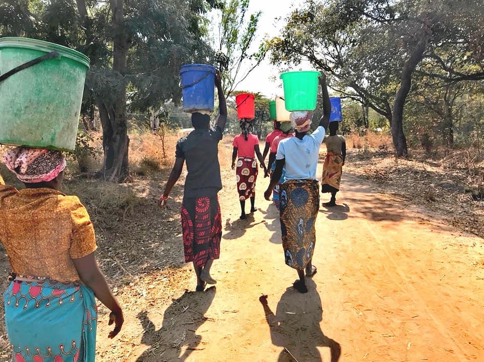 水くみ帰りのマラウイの女性たち。チテンジ(マラウイの伝統布)を腰と頭に巻く(マラウイ・コタコタで撮影 height=