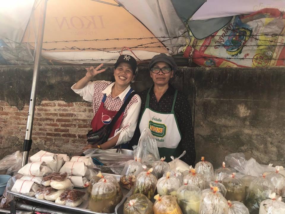 BTSオンヌット駅付近で弁当を売る女性(左)。多くの人が彼女が作るラープ(肉を魚醤とライムで味付けしたもの)や焼き飯を買いに来る