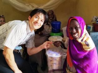 自分で作ったクッキーで起業した障がいをもつ女性とJICA専門家の田島賢侍さん(左)。スーダン西部のダルフール地方で撮影