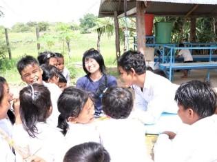 カンボジア・シェムリアップ州にある「プレイキションはちどり小学校」で子どもたちと本を読む宮手恵さん(中央)