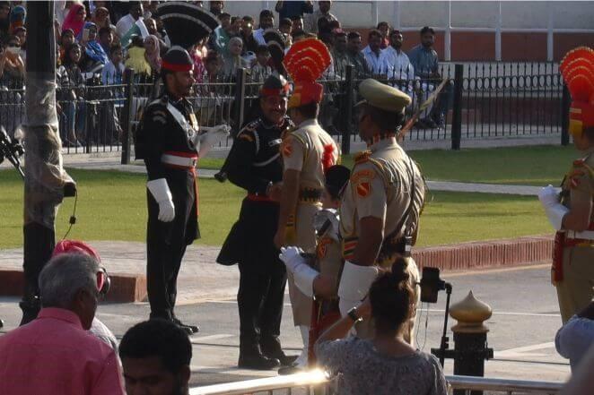 国旗降納後、国境越しに笑顔で握手を交わす印パの国境警備隊。オリーブ色の服がインド、黒色の服がパキスタン。握手をする国境警備隊の足元に見える白線が国境線