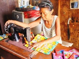 ハロハロの協働団体で、セブ島タリサイ市に拠点を置くNGOブリッジオブライフ(現地名:トゥライサキナブヒ)には現在、2人の裁縫メンバーと3人のオリガミ(お菓子の袋を折る)メンバーがいる。サラさん(写真)はグレマーさんの母親。ジュースのパックを原料とするかばん作りは手慣れている。あっという間に完成した