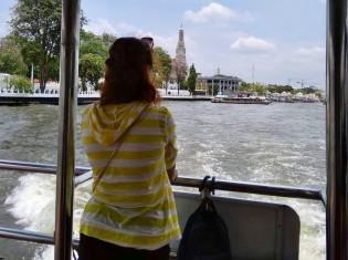 バンコク在住の外国人に人気のベビーシッター、チョーさん。週6日、朝7時から夜7時まで働く。写真は、バンコクの観光地ワットアルンを休みの日に訪れたチョーさん(チャオプラヤ川の舟の上で撮影)