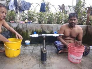 タップ(青と白のもの)が取り付けられた公共の給水所で水浴びする男性。これまでタップがなく、水が流れっぱなしだったのが驚きだ(提供:フィックス・フォー・ライフ)