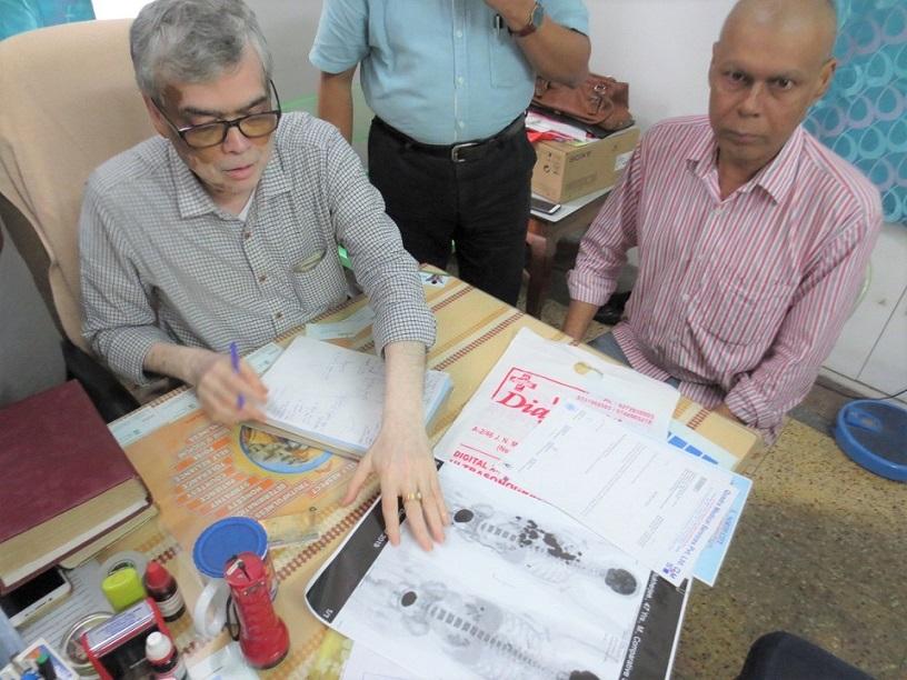 診察中のサーカール医師(左)とムッガルジーさん。机上には画像検査結果のコピーが見える