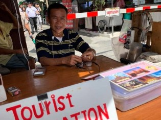 タイサッカーを熱く語るサマーイ・ソンガートさん。バンコク中心部に近いプラトゥナム市場の案内所で働く
