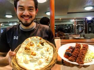 イラク料理「イラク・レストラン・バンコク」の2代目経営者のアナン・コシサギさん。両手に持つのは、店で一番人気のビーフケバブとナンのセット(店内で撮影)