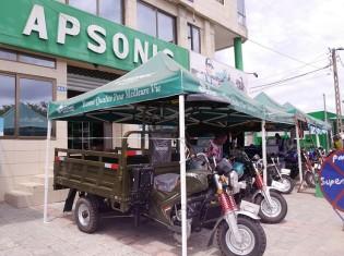 ベナン最大の都市コトヌーにあるアプソニックの社屋の外観。テントには「Bonne qualité pour meilleur vie (より良い生活のための良い品質)」の文字が。手前に見えるのは、アプソニックの主力製品である荷台付き三輪バイク