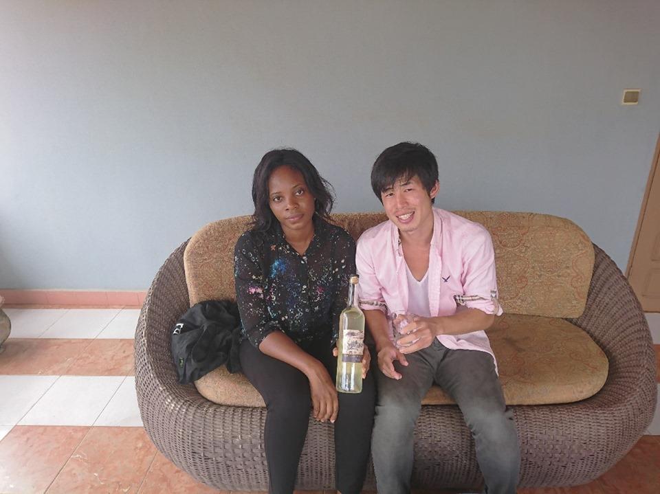 リロリアさん(左)と筆者(右)。トウモロコシ酒を試飲した筆者はベナンのお土産に2本購入した(ベナン・アボメカラビのホテルで撮影)