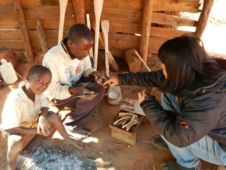 木工カトラリーの制作を担当する村人のもとを訪れ、改良点を説明する徳竹さん(写真右)