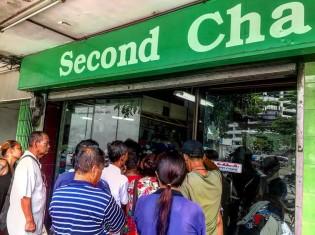 リサイクルショップが開店した瞬間。安くても良いものを手に入れよう、とスラムの住民が一気に押し寄せる(バンコクのクロントイ・スラム)